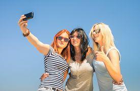 foto of  friends forever  - Happy girlfriends taking selfie against blue sky  - JPG