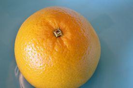 picture of valencia-orange  - A single valencia orange in a blue bowl closeup - JPG