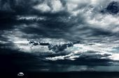 image of flood-lights  - Alone white little boat on sea and dark storm clouds - JPG