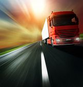 foto of lorries  - Red truck on blurry asphalt road over cloudy sky background - JPG