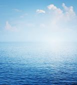 Clear blue sea surface with ripples and sky with fluffy clouds poster