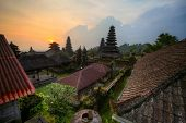 Yard with green trees and buildings of indonesian old temple Pura Besakih at sunset light. Bali. HDR