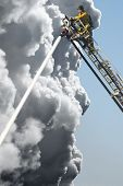stock photo of firehose  - A Fire Man on a lift up high hosing a fire below him - JPG