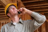 stock photo of engineering construction  - A handsome construction worker on the job and on the phone - JPG
