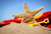 image of sunny beach  - Big starfish in the sand with shovel and beach towel - JPG
