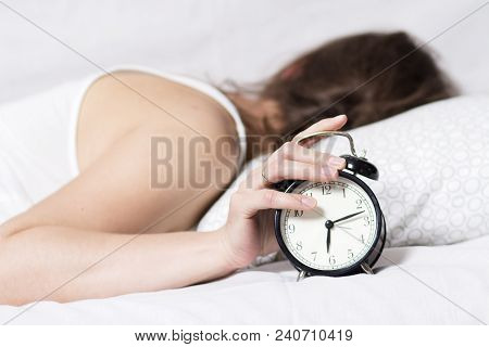 poster of Girl Is Sleeping On Bed In Bedroom And Turns Off Alarm Clock. Woman Does Not Want To Wake Up In Earl
