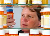 Middle Aged Caucasian Woman Reading Medication Label On Prescription Bottle In Medicine Cabinet, Vie poster