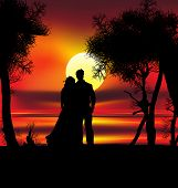 image of heart shape  - Two lovers on the beach with tropical sunset palms sea and island behind them - JPG