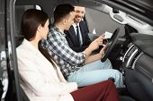 Salesman Consulting Young Couple In Auto At Dealership. Buying New Car poster
