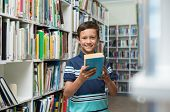 Happy smiling boy reading a book in the library at school. Portrait of cute child in a bookstore loo poster