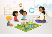 Smiling Female Kindergarten Teacher And Children Sit On Floor And Explore Toy Model With Renewable O poster