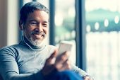 Portrait Smiling Attractive Mature Man Retired With White Stylish Short Beard Using Smartphone Or Li poster