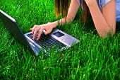 stock photo of online education  - woman connecting the internet with her laptop at the park  - JPG