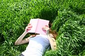 foto of girl reading book  - beautiful woman lays on green field and reads book - JPG