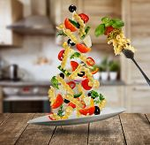 Flying Italian fusilli pasta with ingredients. Concept of low gravity food. Served on wooden table,  poster