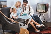 Happy 1950s Style Family Sitting On Sofa And Reading Book Together poster