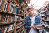 Student Stands In An Atmospheric Library With Books In His Hands And Looks At The Camera. Portrait O poster