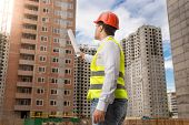 Architect Standing On Building Site And Pointing On Buildings Under Construction With Blueprints poster