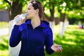 Brunette Girl Drinks Drinking Water From Bottle In Green Summer Park. Healthy Lifestyle. Drinking Cl poster