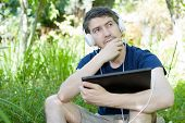 young man relaxing with a tablet pc listening music with headphones on a the park, outdoor poster