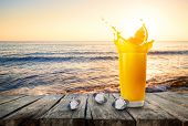 Glass Of Orange Juice With Splash From Orange Slice And Ice Against The Background Of The Sea. Glass poster