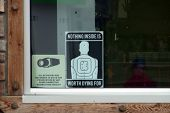 Under Surveillance Sign And Nothing Inside Is Worth Dying For Sign On The Window Of A Convenience St poster