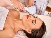 Ultrasonic facial treatment on ultrasound face machine. Woman receiving electric lift massage at spa poster