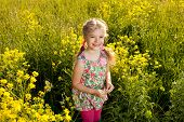 Funny Little Girl Among Yellow Wildflowers