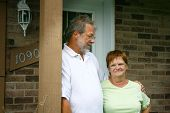 stock photo of old couple  - Senior couple standing outside in front of their house - JPG