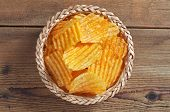 Salty Ribbed Potato Crisps In A Wicker Bowl On The Wooden Table, Top View poster