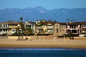 Residential Homes Besides A Sandy Beach And The Pacific Ocean With The San Gabriel Mountains Beyond  poster