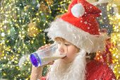Santa Claus Holding Christmas Cookies And Milk Against Christmas Tree Background. Milk And Cookies F poster