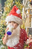 Santa Claus Eating Cookies And Drinking Milk On Christmas Eve. Happy Santa Claus Eating A Cookie And poster