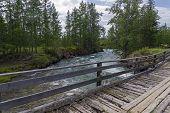 Old Wooden Bridge Over The Fast River. Zhom-bolok River, East Sayan, Buryatia, Siberia, Russia. poster