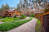 stock photo of house woods  - Big wooden mansion in pine forest - JPG