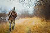 Male Hunter Walking On The Road In The Forest In Autumn. The Gun In The Case On The Shoulder Of The  poster
