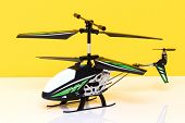 Closeup Of A Little Remote Controlled Toy Helicopter On A Bright Table Against Yellow Background. Ma poster