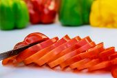 Red Bell Pepper Sliced In Thin Slices On A White Background. poster