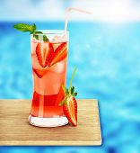 Strawberry juice on the poolside, fresh red berry tropical cocktail on wooden tray, cafe outdoor, be