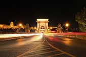 Low Perspective View Of Illuminated Chain Bridge. The Buda Castle (royal Palace) In The Background.  poster