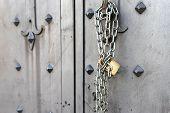 Closeup Of Old Iron Door With Closed Padlock On A Chain. A Chain Of Silver Color With Closed Padlock poster