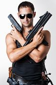 stock photo of tommy-gun  - Handsome sexy military man wearing black fashion sunglasses with automatic and hand gun - JPG