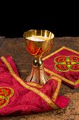 Red damask vestment set of burse and chalice veil, plus chalice filled with holy wafers or hosts