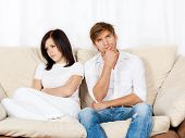 picture of conflict couple  - beautiful young couple conflict sitting on a couch argue unhappy - JPG