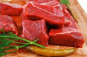 raw fresh beef meat fillet on a wooden plate with dill , hot green red peppers isolated over white b