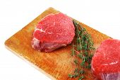 raw red meat : two fresh beef fillet chops with small thyme twig on wooden plate . isolated over whi