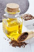 stock photo of flax seed oil  - Linseed oil in a glass bottle and flax seeds on a wooden background - JPG