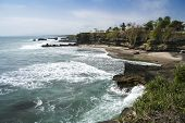 stock photo of tanah  - beach surrounded by cliffs on scenic coastline of tanah lot in bali indonesia - JPG