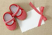 stock photo of christening  - Red shoes and blank note on brown background - JPG