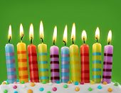 foto of sprinkling  - Ten colorful candles on green background - JPG